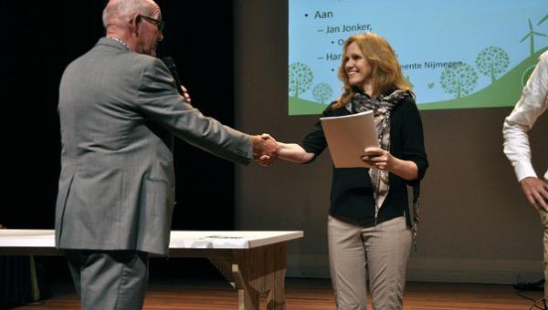 Harriet Thiemens reikt handboek energie opwek uit tijdens Duurzaamheidscafe Nijmegen